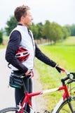 Τον ποδηλάτη, που κατεβαίνουν από το ποδήλατό του, έχει το κράνος στο βραχίονα Στοκ Φωτογραφίες