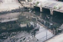 Τοξικό νερό που τρέχει από τους υπονόμους στο βρώμικο υπόγειο υπόνομο για τον καθαρισμό σηράγγων αγωγών εκβάθυνσης στην πόλη Στοκ Φωτογραφία