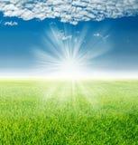 Τοπίο άνοιξη, πράσινη χλόη κάτω από τις ακτίνες του ήλιου αύξησης Στοκ φωτογραφία με δικαίωμα ελεύθερης χρήσης