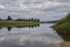 Τοπίο Ένας όμορφος, ευρύς ποταμός με την αντίθεση καλύπτει στον ουρανό και ένα γραφικό χωριό στην αντίθετη ακτή διανυσματική απεικόνιση