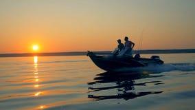 Τοπίο ανατολής με δύο ψαράδες που οδηγούν motorboat Φιλία, έννοια καλύτερων φίλων απόθεμα βίντεο