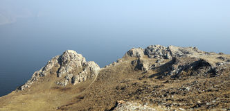 Τοπίο βουνών, ηφαιστειακοί βράχοι στο πρώτο πλάνο ενάντια στον μπλε ουρανό φθινοπώρου σε μια ελαφριά ομίχλη Στοκ Εικόνα