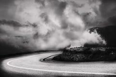 Τοπίο βουνών με έναν δρόμο στο πρώτο πλάνο, σε μια γραπτή ερμηνεία Στοκ Φωτογραφίες