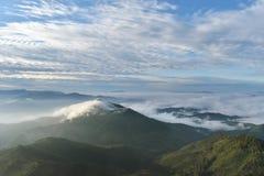 Τοπίο βουνών με την ομίχλη, το σύννεφο και τη δασικά ανατολή και το ηλιοβασίλεμα στα βουνά στοκ φωτογραφία