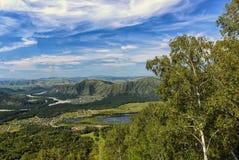 Τοπίο βουνών με τη λίμνη και το χωριό Στοκ Εικόνες