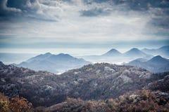 Τοπίο βουνών με τις αιχμές βουνών στην παραλία με το δραματικό ουρανό στη συννεφιάζω ημέρα με την υδρονέφωση στη χώρα Μαυροβούνιο Στοκ φωτογραφίες με δικαίωμα ελεύθερης χρήσης
