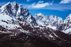 Τοπίο βουνών χιονιού ενάντια στο μπλε ουρανό Στοκ Εικόνες