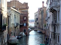 Τοπίο ενός στενού καναλιού στη Βενετία με τις βάρκες από τα κτήρια που σταθμεύουν Στοκ Εικόνες