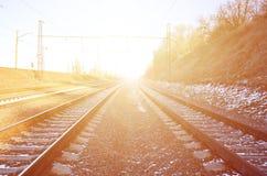 Τοπίο ενός χιονώδους ρωσικού χειμερινού σιδηροδρόμου κάτω από το φωτεινό φως του ήλιου οι ράγες και οι κοιμώμεοί κάτω από το χιόν Στοκ Εικόνα