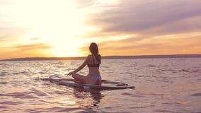 Τοπίο ηλιοβασιλέματος με μια πανέμορφη συνεδρίαση γυναικών σε ένα paddleboard καρπός ρολογιών χαλάρωσης τσεπών χεριών έννοιας απόθεμα βίντεο