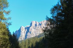 Τοπίο με ένα πράσινο δάσος, τα βουνά και το μπλε ουρανό Στοκ Φωτογραφίες