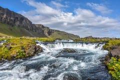 Τοπίο με λίγο καταρράκτη, την πράσινα χλόη και τα βουνά Στοκ Φωτογραφίες