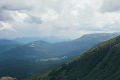 Τοπίο με τα βουνά, το δασικό και νεφελώδη ουρανό Στοκ Φωτογραφίες