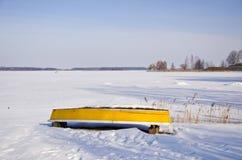 Κίτρινη βάρκα στην ακτή χειμερινών λιμνών Στοκ Φωτογραφίες