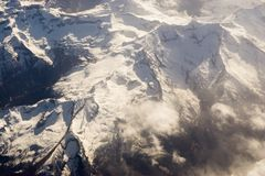 Τοπίο με τις αιχμές που καλύπτονται από το χιόνι και τα σύννεφα Στοκ Εικόνες