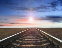 Τοπίο με τις ράγες που πηγαίνουν μακριά στο ηλιοβασίλεμα και που εξισώνουν τον ήλιο Στοκ Φωτογραφία