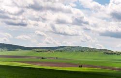 Τοπίο με τους τομείς γεωργίας και τις πράσινες περιοχές μια ηλιόλουστη ημέρα με το νεφελώδη ουρανό στοκ εικόνα