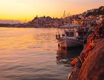 Τοπίο μιας πόλης, μιας βάρκας και μιας θάλασσας στο ηλιοβασίλεμα Στοκ Φωτογραφίες