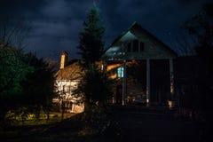 Τοπίο νύχτας βουνών του κτηρίου στο δάσος τη νύχτα με το φεγγάρι ή το εκλεκτής ποιότητας εξοχικό σπίτι τη νύχτα με τα σύννεφα και στοκ φωτογραφία