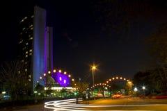 Τοπίο νύχτας στη μακροχρόνια έκθεση Ψηλό κτίριο και αυτοκίνητα που περνούν τα φω'τα νύχτας στοκ εικόνα