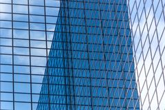 Τοπίο πόλεων - δείτε από κάτω από στους ουρανοξύστες γυαλιού με τον απεικονισμένο ουρανό στα παράθυρα στοκ εικόνα