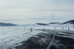 Τοπίο της κενής οδικής στροφής ασφάλτου που αφήνεται μέσω του τομέα και του λόφου χιονιού Στοκ Φωτογραφίες