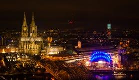 Τοπίο της νυχτερινής Κολωνίας με τα φωτεινά φω'τα στον καθεδρικό ναό, τον πύργο TV, και τη γέφυρα Hohenzoller Στοκ Φωτογραφίες
