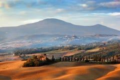 Τοπίο της Τοσκάνης στην ανατολή Tuscan αγροτικό σπίτι, δέντρα κυπαρισσιών, λόφοι Στοκ Εικόνες