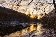 Τοπίο του άγριου ποταμού με την αντανάκλαση ουρανού ηλιοβασιλέματος στα βουνά, το χειμώνα Στοκ Φωτογραφία
