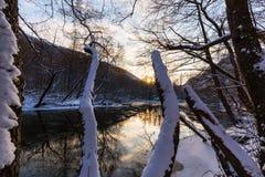 Τοπίο του άγριου ποταμού με την αντανάκλαση ουρανού ηλιοβασιλέματος στα βουνά, το χειμώνα Στοκ Εικόνα