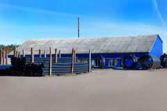 Τοπίο των μπλε σωρών σωλήνων αποθηκών εμπορευμάτων και PVC μαύρων πλαστικών για τα υδραυλικά στο μέτωπο το κτήριο Στοκ φωτογραφίες με δικαίωμα ελεύθερης χρήσης