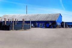 Τοπίο των μπλε σωρών σωλήνων αποθηκών εμπορευμάτων και PVC μαύρων πλαστικών για τα υδραυλικά στο μέτωπο το κτήριο Στοκ εικόνα με δικαίωμα ελεύθερης χρήσης