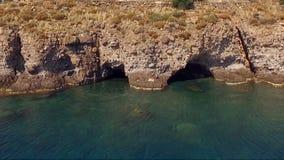 Τοπίο των grottoes στους απότομους βράχους, βουνά, απότομοι βράχοι Το νερό έπλυνε τα βαθιά grottos Ελληνικά νησιά στη Μεσόγειο απόθεμα βίντεο