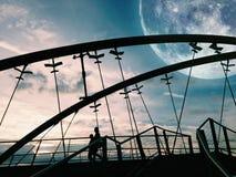 Τοπίο φαντασίας - σκιαγραφίες δύο ανθρώπων που περπατούν μια γέφυρα W Στοκ Εικόνα