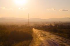 Τοπίο φθινοπώρου ή χειμώνα με το δρόμο και τα δέντρα Το χρυσό ηλιοβασίλεμα ελαφριών ακτίνων Σε ένα υπόβαθρο των βουνών και τον ου Στοκ εικόνα με δικαίωμα ελεύθερης χρήσης