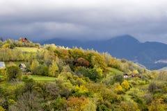 Τοπίο φθινοπώρου με τα ζωηρόχρωμους δέντρα και τους λόφους Στοκ Φωτογραφία