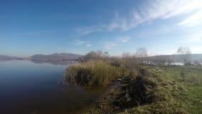 Τοπίο φθινοπώρου στην όχθη της λίμνης με τον ήλιο και το μπλε νερό φιλμ μικρού μήκους