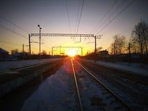 Τοπίο φωτογραφιών ενός σιδηροδρόμου με μια πλατφόρμα το βράδυ με τον ήλιο στο ηλιοβασίλεμα Στοκ Φωτογραφία