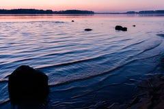 Τοπίο χαλάρωσης με ένα ρόδινο ηλιοβασίλεμα σε έναν κυματιστό ποταμό και τις σκιαγραφίες των μεγάλων πετρών στοκ εικόνες