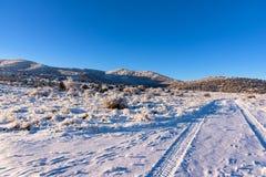 Τοπίο χειμερινού ηλιόλουστο μπλε ουρανού με τις διαδρομές και το βουνό αυτοκινήτων Στοκ φωτογραφίες με δικαίωμα ελεύθερης χρήσης
