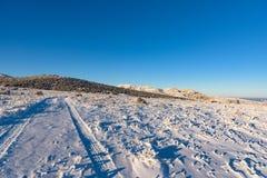 Τοπίο χειμερινού μπλε ουρανού με τις διαδρομές, βουνό Στοκ φωτογραφία με δικαίωμα ελεύθερης χρήσης