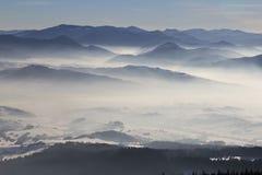 Τοπίο χειμερινών βουνών - άποψη του χιονιού, καλυμμένη υδρονέφωση κοιλάδα Στοκ φωτογραφία με δικαίωμα ελεύθερης χρήσης