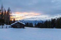 Τοπίο χιονιού του νότιου Tirol montains και ξύλινη καμπίνα στο ηλιοβασίλεμα Στοκ Εικόνα