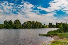 Τοπίο, όμορφο καλοκαίρι Ένα χωριό στις όχθεις ενός ευρύ ποταμού, όμορφες, σωρείτης καλύπτει σε έναν μπλε ουρανό μια θερινή ημέρα στοκ φωτογραφίες με δικαίωμα ελεύθερης χρήσης