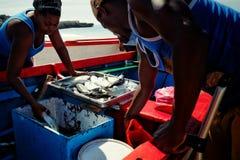 τοπικός ψαράς που ξεφορτώνει τη σύλληψή του ενώ η γυναίκα από την αγορά πρόκειται προς τα εμπρός να ελέγξει τα ψάρια του στοκ φωτογραφία