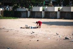 Τοπικό άτομο που καθαρίζει μια βρώμικη παραλία στοκ εικόνες