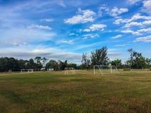 Τοπικό γήπεδο ποδοσφαίρου με τη θέση στόχου και το μπλε ουρανό και λευκό clo Στοκ Εικόνες