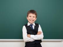 Τοποθέτηση αγοριών σχολικών σπουδαστών στον καθαρό πίνακα, μορφασμός και συγκινήσεις, που ντύνονται σε ένα μαύρο κοστούμι, έννοια Στοκ Εικόνες