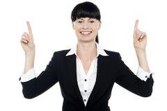 Τοποθέτηση γυναικών χαμόγελου με τα αυξημένα δάχτυλα Στοκ Εικόνες
