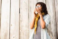 Τοποθέτηση γυναικών χαμόγελου περιστασιακή με τα γυαλιά πίνοντας τον καφέ Στοκ Εικόνα